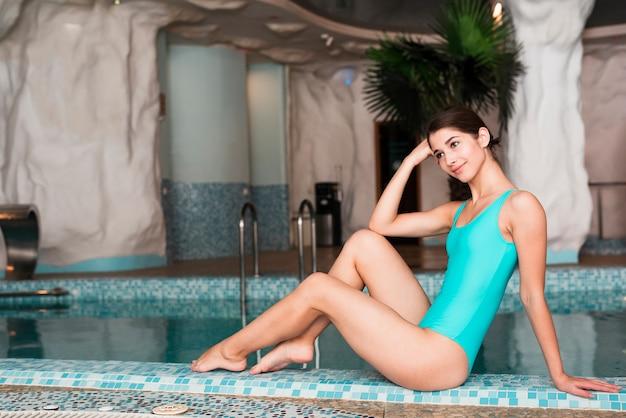 Mujer en traje de baño posando junto a la piscina
