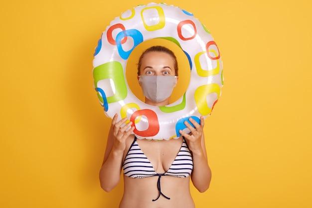 Mujer en traje de baño a rayas mirando a través del anillo de goma, usando una mascarilla higiénica para prevenir el virus en la playa del complejo, el descanso y las vacaciones de verano con medios para proteger su salud