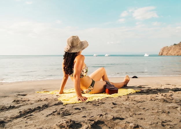 Mujer en traje de baño tomando el sol con ukelele en la playa