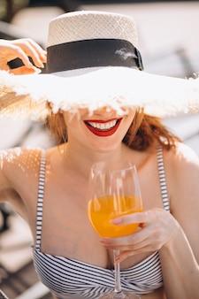 Mujer en traje de baño en vacaciones bebiendo jugo