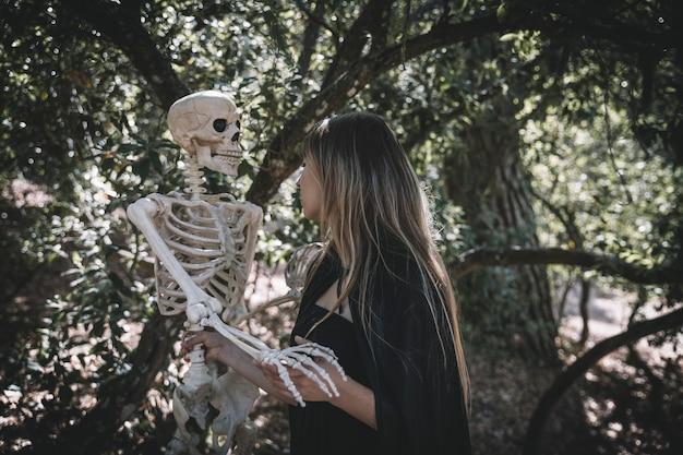Mujer en traje de bruja con espeluznante esqueleto