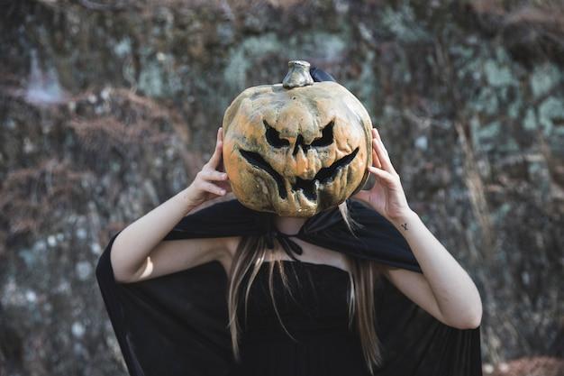 Mujer en traje de bruja que cierra la cara por calabaza espantosa