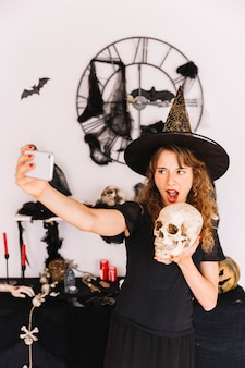 Mujer en traje de bruja que hace selfie con calavera