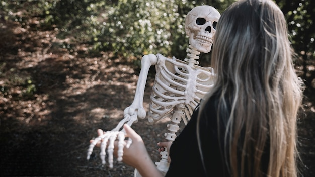 Mujer en traje de bruja que se inclina esqueleto