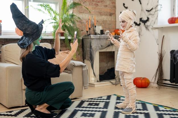 Mujer en traje de bruja tomando fotos de su pequeño hijo