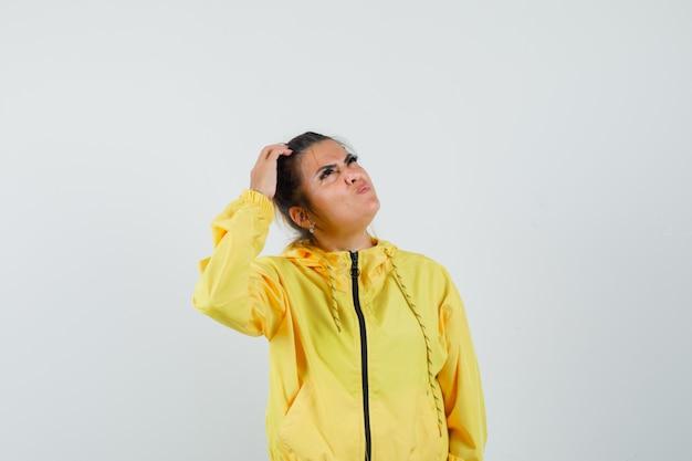 Mujer en traje deportivo mirando hacia arriba mientras se rasca la cabeza y mira pensativa, vista frontal.