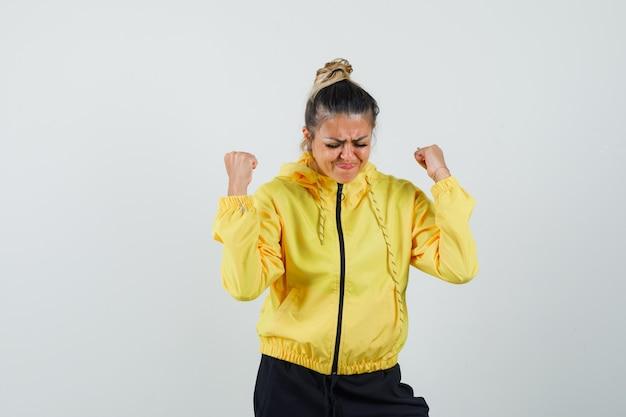 Mujer en traje deportivo mostrando gesto de ganador y con suerte, vista frontal.