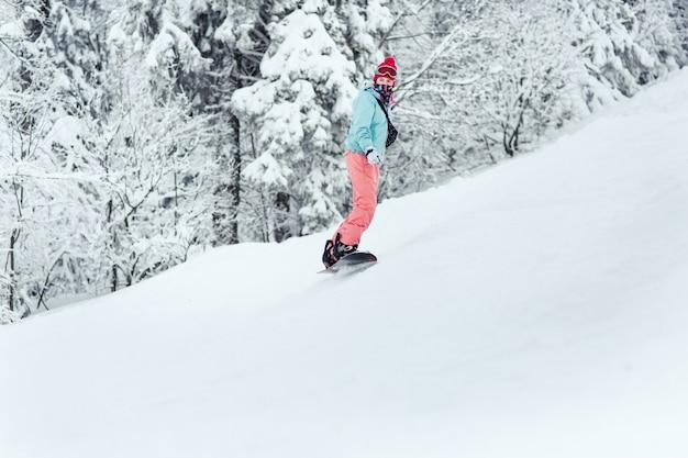 La mujer en traje de esquí mira sobre su hombro bajando la colina en su tabla de snowboard