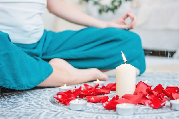Mujer en traje étnico practicando yoga frente a velas quemadas y pétalos de rosas rojas