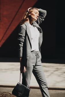 Mujer en traje gris posa con bolsa negra en la calle de nueva york