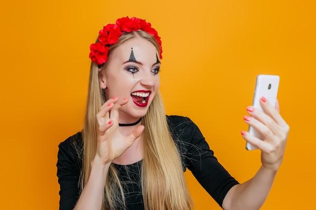 Mujer en traje de halloween hace muecas y mira el teléfono