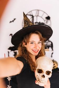 Mujer en traje de halloween con sombrero puntiagudo con calavera