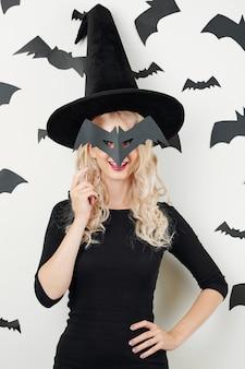 Mujer en traje de hechicera posando con máscara de murciélago