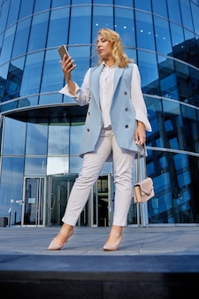 Mujer en traje de negocios se encuentra frente a un edificio de oficinas y mira la pantalla del teléfono inteligente