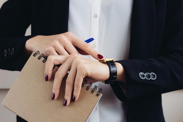 Mujer en un traje de negocios y manicura rojo oscuro que sostiene un cuaderno y mira su primer plano de reloj