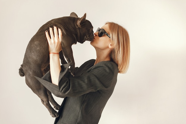 Mujer en un traje negro con bulldog negro