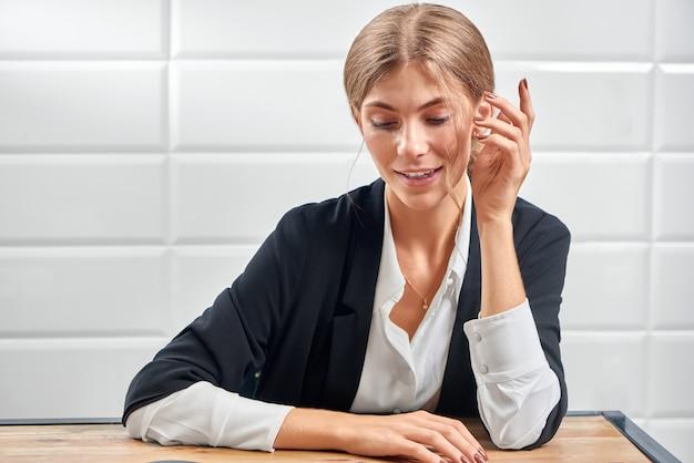 Mujer en traje de oficina sonriendo y mostrando nueva manicura hermosa.