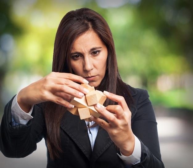 Mujer con traje resolviendo un juego de inteligencia de madera