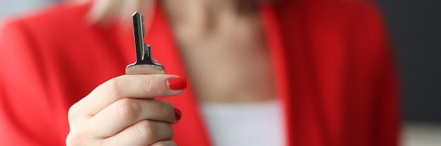 Mujer en traje rojo con llave de acero en primer plano de la oficina. trabajando en concepto de agencia inmobiliaria