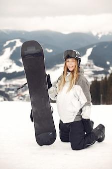 Mujer en traje de snowboard. deportista en una montaña con una tabla de snowboard en las manos en el horizonte. concepto de deportes