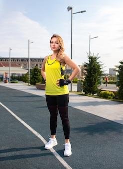 Mujer en trajes deportivos amarillos y negros de pie y posando en una línea de jogging.
