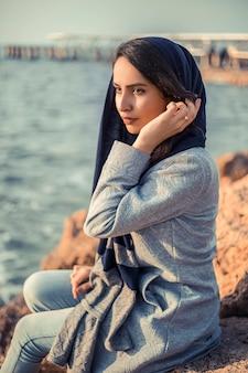 Mujer en trajes de hijab en la orilla del mar