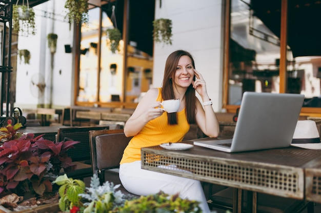 Mujer tranquila en la cafetería de la calle al aire libre sentado en la mesa trabajando en una computadora portátil moderna, beber té, relajarse en el restaurante durante el tiempo libre
