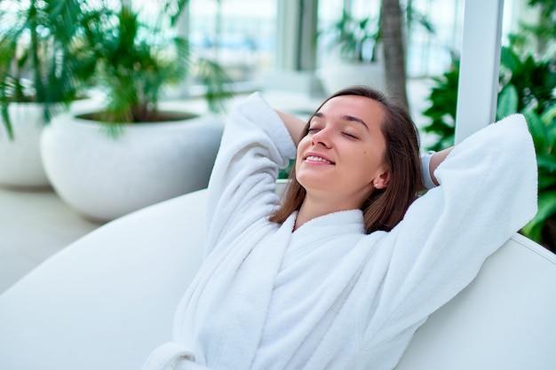 Mujer tranquila serena con albornoz blanco con los ojos cerrados y las manos detrás de la cabeza disfrutando de un momento de relax y sentirse bien en un balneario de bienestar.