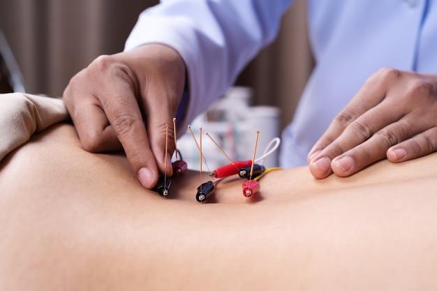 Mujer en tratamiento de acupuntura con estimulador eléctrico en la espalda