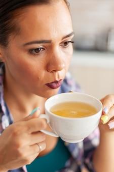 Mujer tratando de beber té verde caliente con hierbas aromáticas en la cocina por la mañana