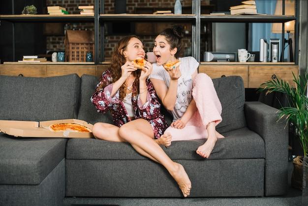 Mujer tratando de comer la pizza de su amigo en casa