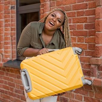 Mujer tratando de levantar un pesado equipaje amarillo