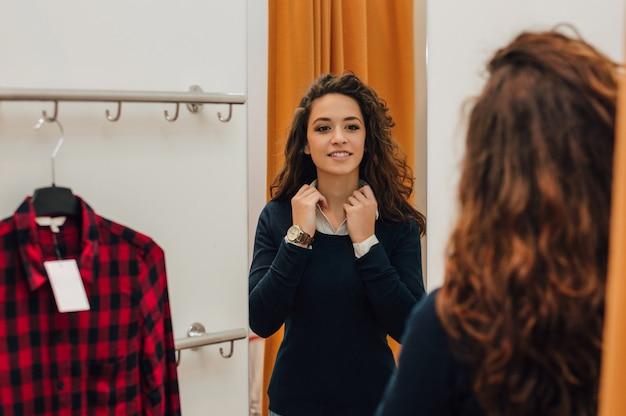 Mujer tratando de ropa en el vestidor.