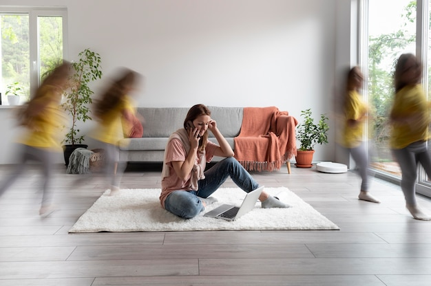 Mujer tratando de trabajar en la computadora portátil desde casa mientras sus hijos corren