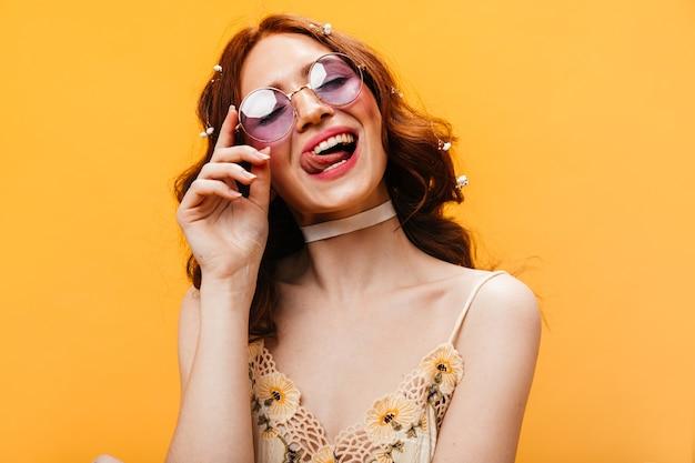 Mujer traviesa con gafas de sol color lila se está lamiendo los labios y posando sobre fondo naranja.