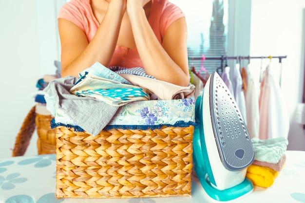 Mujer trayendo una gran pila de ropa en la tabla de planchar