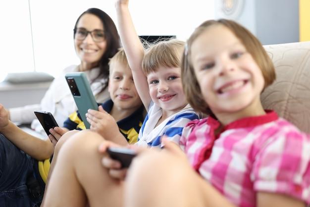 Mujer y tres niños están sentados en el sofá, sonriendo y sosteniendo teléfonos inteligentes en sus manos.
