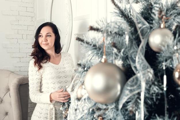 La mujer triguena bastante joven que se colocaba cerca de abeto en navidad adornó el sitio.