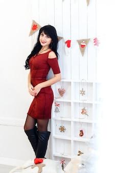 La mujer triguena joven atractiva en vestido rojo sitanding en una navidad adornó el interior.