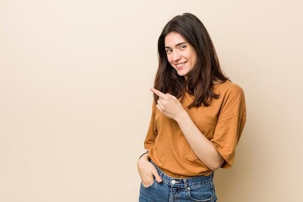 Mujer triguena joven contra un beige que sonríe y que señala a un lado, mostrando algo en blanco.