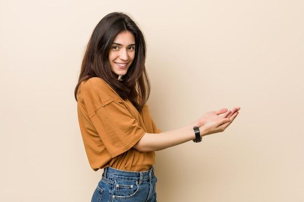 Mujer triguena joven contra un fondo beige que lleva a cabo un espacio de la copia en una palma.