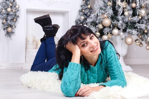 La mujer triguena joven feliz que miente en un piso dentro en navidad adornó el interior.
