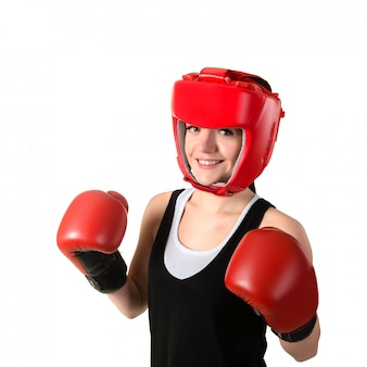 Mujer triguena joven en guantes de boxeo rojos y casco que hace impacto, mirando la cámara.