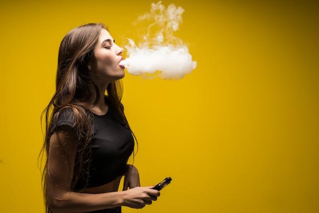 Mujer triguena joven que se coloca y vaping aislada en la pared amarilla.