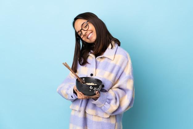 La mujer triguena joven que sostiene un cuenco lleno de fideos sobre azul aislado mantiene la palma unida.