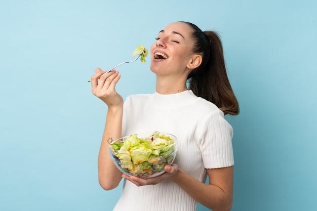 Mujer triguena joven que sostiene una ensalada sobre la pared azul aislada
