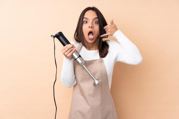 Mujer triguena joven que usa la licuadora de la mano que hace gesto del teléfono y dudando