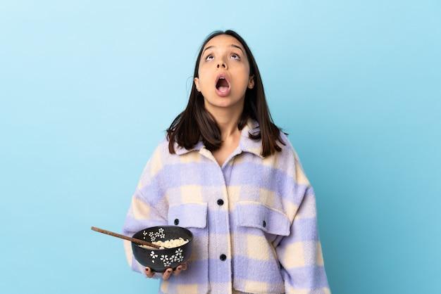 Mujer triguena joven de la raza mixta que sostiene un cuenco lleno de fideos sobre la pared azul que mira para arriba y con la expresión sorprendida.