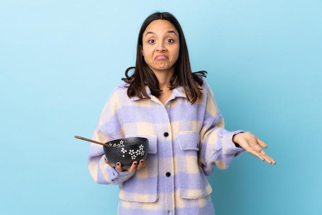Mujer triguena joven de la raza mixta que sostiene un cuenco lleno de fideos sobre la pared azul que tiene dudas mientras que levanta las manos.