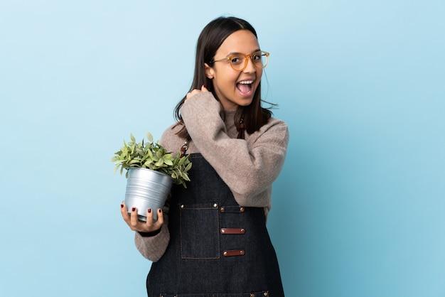 Mujer triguena joven de la raza mixta que sostiene una planta sobre la pared azul que celebra una victoria.